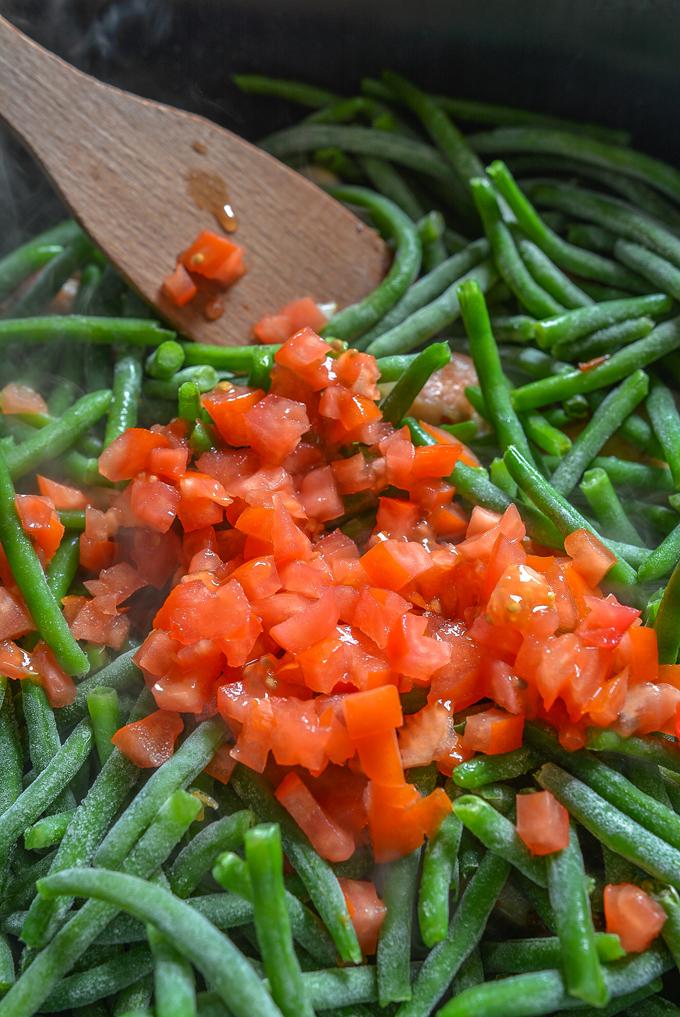 הוספת קוביות עגבניה לשעועית הירוקה